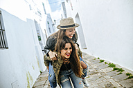 Happy young woman giving friend a piggyback ride - KIJF01136