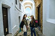 Spain, Andalusia, Vejer de la Frontera, two young women walking in the alley El Callejon de las Monjas - KIJF01148
