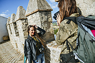 Young traveling women recording with old video camera - KIJF01160