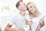 Man holding cup of coffee kissing woman - WESTF22528
