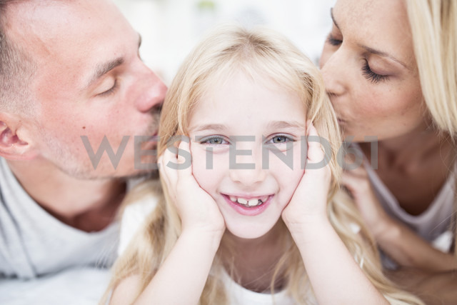 Portait of smiling girl being kissed by parents - WESTF22531