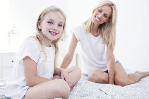 Portait of smiling girl sitting on bed with mother - WESTF22534