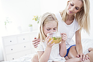 Mother watching daughter drinking cup of tea on bed - WESTF22537