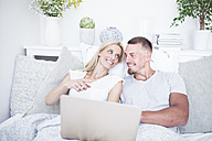 Relaxed couple in bed using laptop - WESTF22549