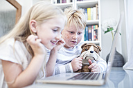 Brother and sister with cuddly toy using laptop together - WESTF22555