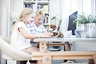Brother and sister with cuddly toy using laptop together - WESTF22558