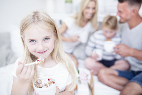 Portrait of smiling girl eating from cereal bowl with family in background - WESTF22567