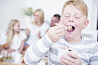 Boy eating from cereal bowl with family in background - WESTF22570