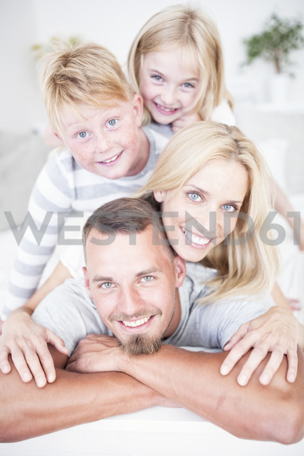 Portrait of smiling family lying in bed on top of each other - WESTF22576