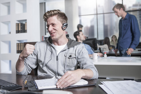 Young man at desk in office wearing a headset - ZEF12495