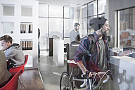 Casual man with bike in modern office - ZEF12504