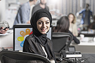 Portrait of smiling young woman wearing hijab in office - ZEF12507