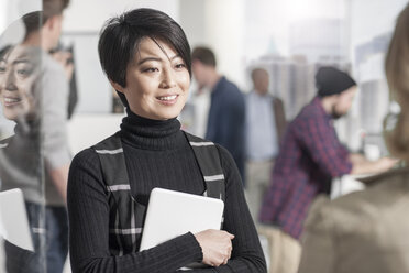 Portrait of smiling woman holding a tablet in office - ZEF12516