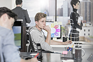 Young man at office desk thinking - ZEF12519