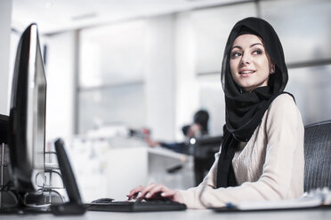 Young woman wearing hijab working on desk in office - ZEF12537