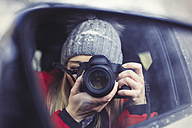 Wing mirror with mirror image of woman taking picture of herself, close-up - JUNF00779