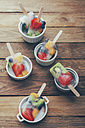 Bowls of fruit ice lollies with fresh fruits on white ground - RTBF00610