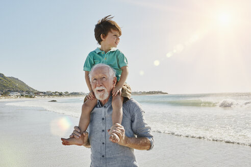 Portrait of senior man with grandson on his shoulders on the beach - RORF00533