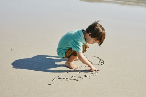 Little boy drawing in the sand on the beach - RORF00539