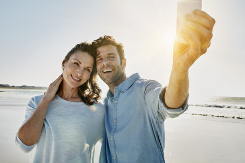 Portrait of happy couple taking selfie on the beach with smartphone - RORF00569