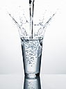 Pouring water into glass in front of white background - RORF00572