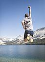 USA, California, Yosemite National Park, back view of man jumping in the air at mountain lake - EPF00298