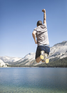 USA, California, Yosemite National Park, back view of man jumping in the air at mountain lake - EPF00298