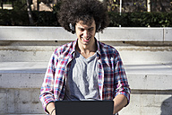 Smiling young man using laptop and headphones - ABZF01798