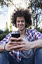 Portrait of smiling young man using smartphone - ABZF01801