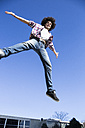 Smiling young man jumping in the air with arms outstretched - ABZF01804