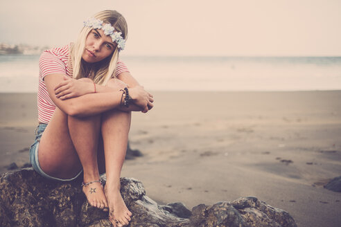 Portrait of young woman wearing flowers sitting on rock on the beach - SIPF01355