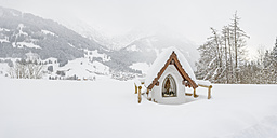 Germany, Bavaria, snow-covered wayside shrine with Rubihorn in the background - WGF01048