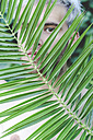 Portrait of naked young man behind palm leaf - RTBF00615
