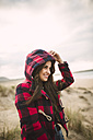 Smiling young woman with long brown hair wearing hooded jacket on the beach - RAEF01680