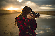 Young woman taking picture on the beach with camera at sunset - RAEF01686