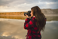 Young woman taking picture on the beach with camera at sunset - RAEF01689