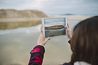 Young woman taking picture with tablet on the beach - RAEF01692