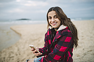Portrait of smiling young woman with smartphone on the beach - RAEF01695