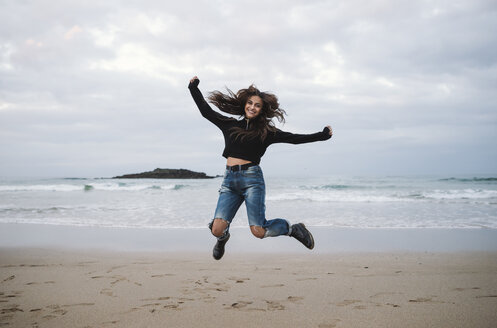 Happy woman jumping in the air on the beach - RAEF01698