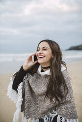 Portrait of happy young woman on the phone on  the beach - RAEF01704