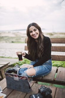 Portrait of smiling young woman with glass of Cola in an outdoor cafe - RAEF01707
