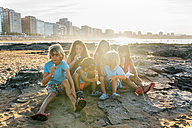 Group of six children eating icecream on the beach - MGOF02821