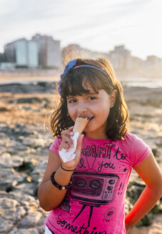 Portrait of smiling little girl eating  icecream on the beach at sunset - MGO02824