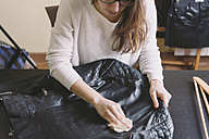 Woman cleaning leather jacket - SKCF00247