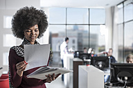 Woman looking at documents in office - ZEF12552