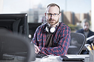 Portrait of confident man at desk in office - ZEF12591