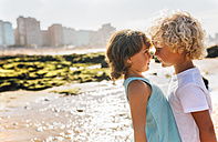 Little boy and girl face to face on the beach - MGOF02840