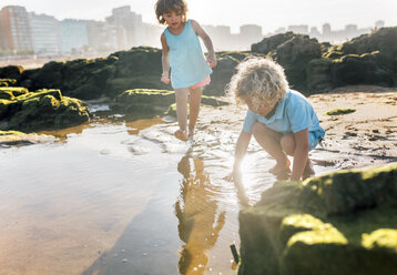 Little boy and girl playing together on the beach - MGOF02858