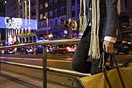 Man holding bag and using his cell phone in a street at night - ABZF01811