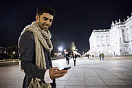 Man using his cell phone in the city at night - ABZF01826
